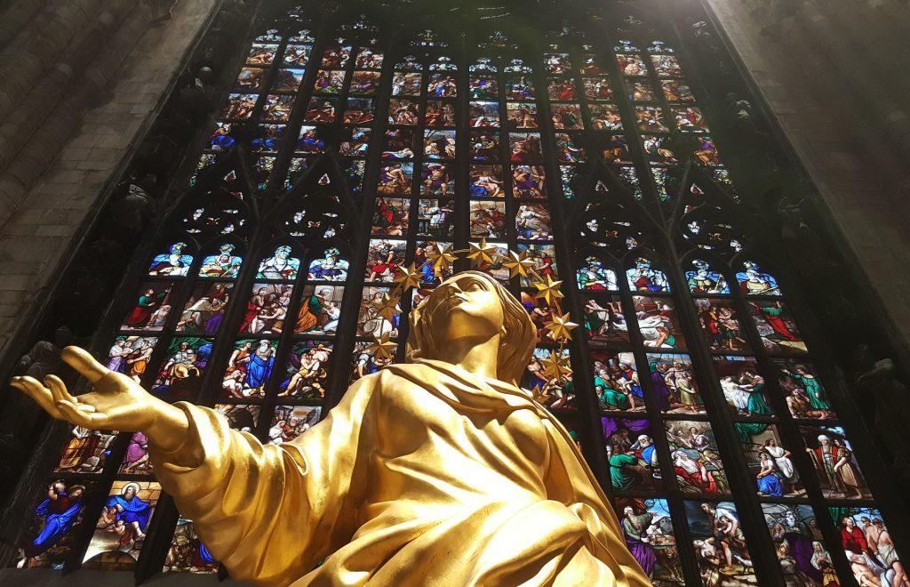 Réplica de la Madonnina de Oro junto a los vitrales del Duomo de Milán